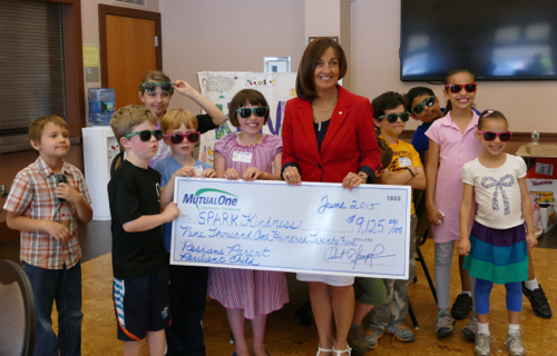 Rachel Stewart (center), administrative director, MutualOne Charitable Foundation, celebrating the Foundation's grant to SPARK Kindness along with children from the program.