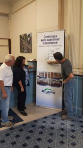 Construction worker showing Bank employees the Natick office renovation floor plan