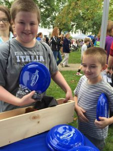 Boy holding MutualOne Bank frisbee at Natick Days