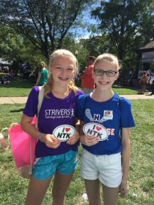 "Girls holding ""I heart Natick"" signs at Natick Days"