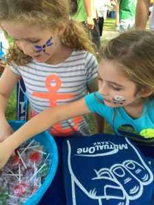 Girls taking candy from MutualOneBank booth at Natick Days