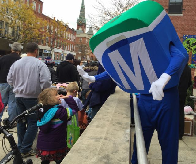 Mo giving high fives to children in the Natick Halloween Parade