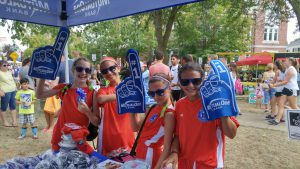 Tweens wearing foam fingers at MutualOne Bank's booth at Natick Days