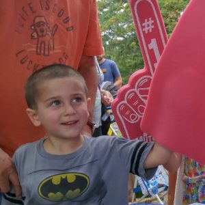 Young boy wearing foam fingers at MutualOne Bank's booth at Natick Days