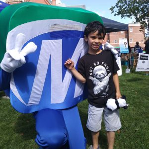 Natick Days Mo with boy giving peace sign