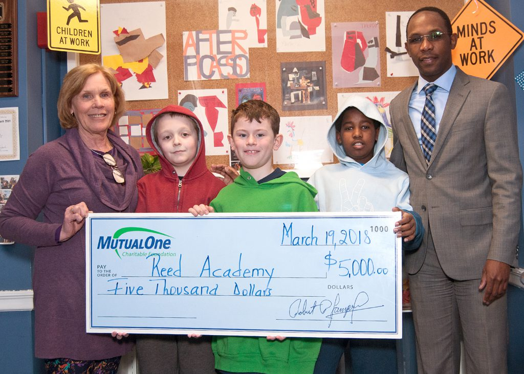 Reed Academy Executive Director Mary Crawford; MutualOne Bank Charitable Foundation Administrator Yves Munyankindi and Reed Academy students Nick Grant, Alex Williams and Henry Barry celebrate the Foundation's recent $5,000 award.
