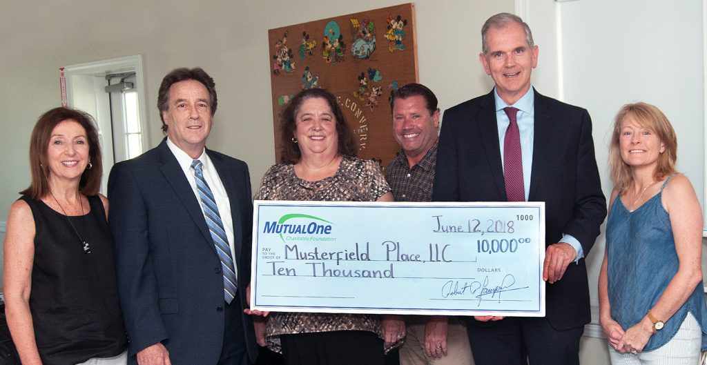 MutualOne Charitable Foundation's $10,000 grant to Musterfield Place is celebrated by (l-r) Janice Rogers, commissioner of the Framingham Housing Authority; Mark Haranas, president and CEO of MutualOne Bank; Darlene Herweck, property manager at Musterfield Place; Ryan Carey, activity coordinator at Musterfield Place; Paul Landers, executive director and Janet Leombruno, commissioner of the Framingham Housing Authority.
